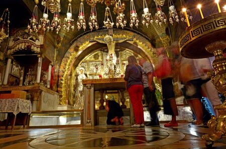 christian altar: JERUSALEM, ISR - MAY 05 2015:Pilgrims at Golgotha  Altar of the Crucifixion at the Church of the Resurrection in Jerusalem, Israel. The Church considered to be the holiest Christian site in the world.