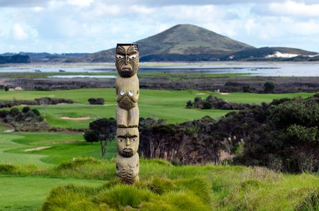 Maori carving against Rangiputa mountain in  Karikari peninsula, New Zealand.