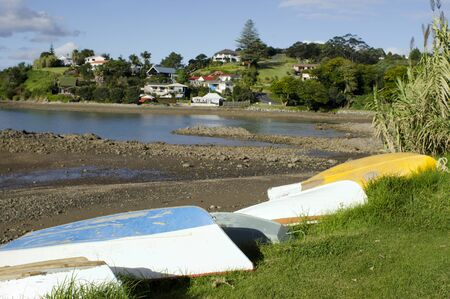 upturned: Upturned old classic colorful dinghy boats on the ground during low tide in Mill Bay and the town of Mangonui, Northland, New Zealand. Stock Photo