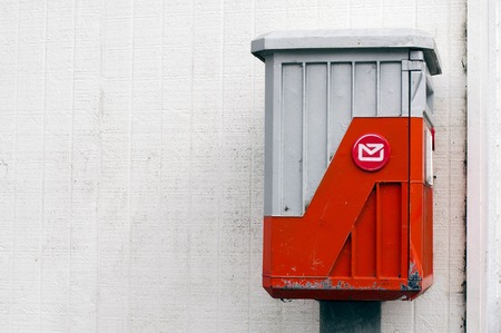 fence post: An old mail box against a white wall with space for copy text. Stock Photo