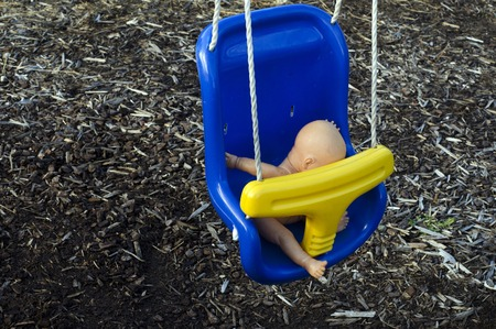 Concept photo of a naked baby doll on a swing in a playground. photo