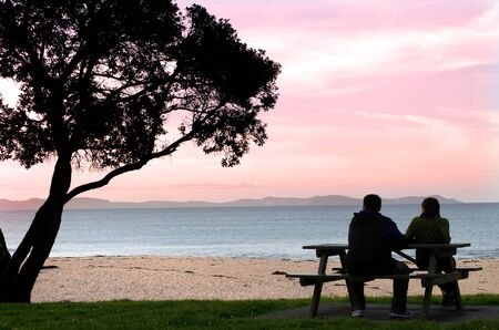 Silhouette of a heterosexual couple enjoying the afternoon with a calm and peaceful relaxing sunset in front of the ocean view. Copyspace above with room for text. photo