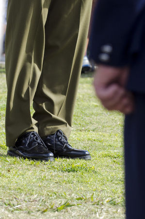 lower body: Lower body of a shiny army shoes and brown uniform during military parade.