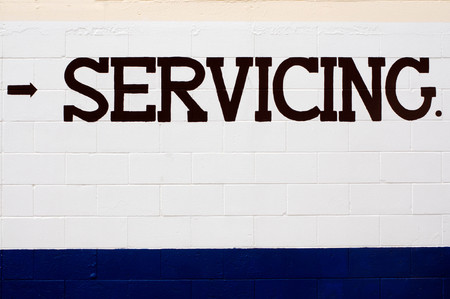 servicing: Servicing wording painted on a white and blue  brick wall with small arrow direction.