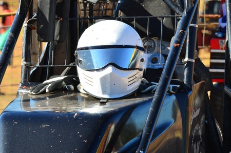 stock car: A white helmet with gloves on a super stock car during a dirt track racing in Taipa speedway, New Zealand.