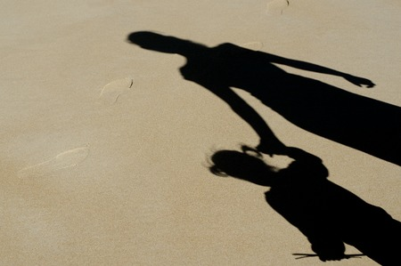 hold: Shadow of mother and her child over a sand on the beach during summer vaction.