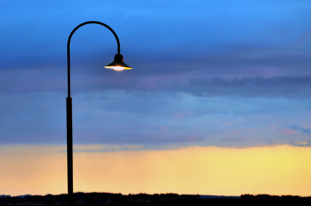 그것의 현대적인 가로등이 일몰 동안 켜져 있습니다.