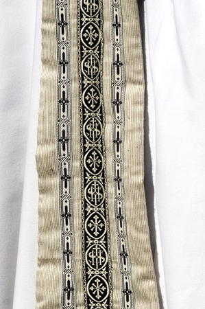 cleric: Close up of priests garment clothing decorated with small crosses on white wearing. Stock Photo