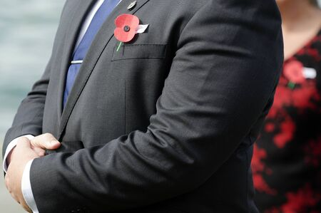 cross armed: Close up of an ANZAC red poppy on a person during a National War Memorial Anzac Day services in New Zealand.