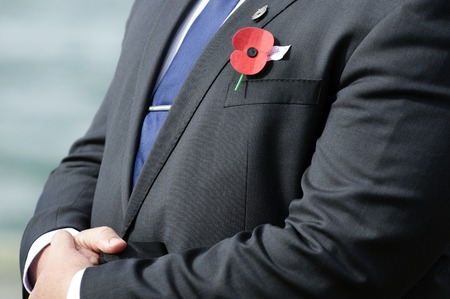 remembrance day: Close up of     red poppy on a person during a   Stock Photo