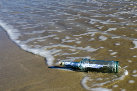 ashore: Message in a bottle washed ashore on a beach.