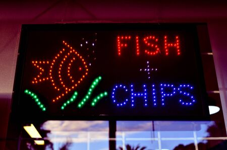 neon fish: A neon lights Fish and Chips place sign. Stock Photo