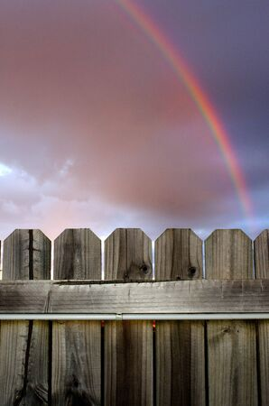 clouds scape: Rainbow in the cloud above a wood fence.