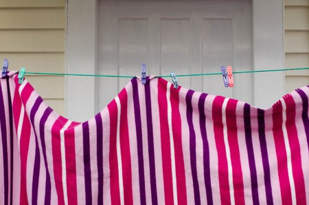 red pink: Clean striped red, pink, purple and lily colors sheets on hanged on a Washing line.