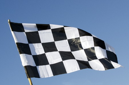 Checkered flag and blue sky during racing in a speedway.