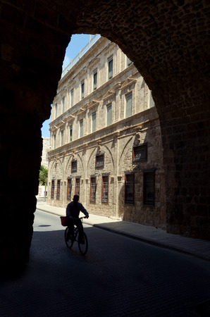 despite: ACRE, ISR - APR 21 2015: Ride a bike under the walls of Akko.Old Acre is one of the few cities in the world whose walls have remained standing despite attacks by large powerful armies several times Editorial