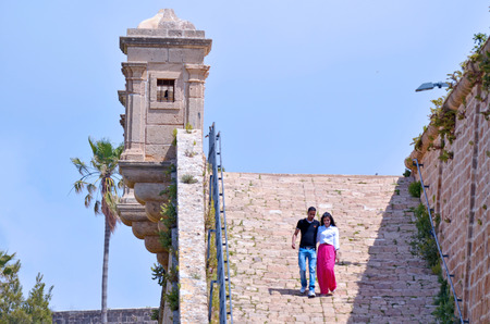 akko: ACRE, ISR - APR 21 2015: Arab couple visit at the walls of Akko.Old Acre is one of the few cities in the world whose walls have remained standing despite attacks by large powerful armies several times Editorial