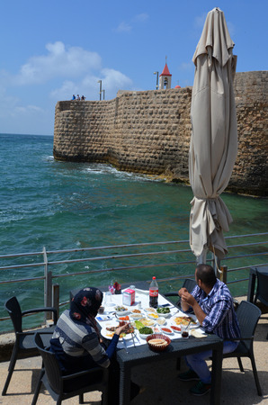 continuously: ACRE, ISR - APR 21 2015:Arab couple dinning in a restaurant in Acre Akko old city port, Israel.Acre is one of the oldest continuously inhabited sites in the world.