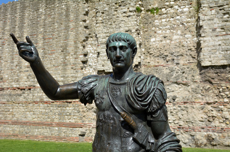 Bronz Statue of Trajan in front of a section of the Roman wall, Tower Hill London, UK.He was Roman emperor (98 -117 AD) presided over the greatest military expansion in Roman history.