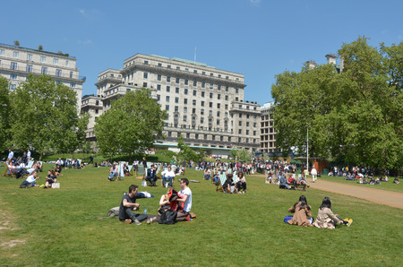 british weather: LONDON - MAY 13 2015:Visitors at Green Park on enjoy a sunny day in London. According to the British weather forecast the average sunny days in London are only 61 days in a year. Editorial