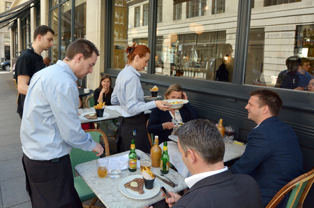 LONDON - MAY 14 2015:Waiters serving food and drinks to people dining in a restaurant in London England UK.The average UK household spends £15.20 a week on restaurants and cafes.