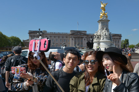 buckingham palace: LONDON - MAY 13 2015:Chines tourists taking a selfie in Buckingham Palace. Its one of most popular tourist attractions in London, UK Editorial