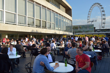 southbank: LONDON, UK - MAY 15 2015:People drinking outside the Royal Festival Hall in with London Eye in the background.Royal Festival Hall is a dance and talks venue within Southbank Centre in London.