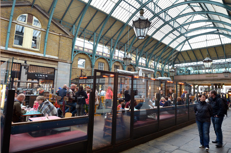 tourist site: LONDON - MAY 15 2015:Visitors in Covent Garden markets. Its one of the most popular shopping center and tourist site in London, UK.