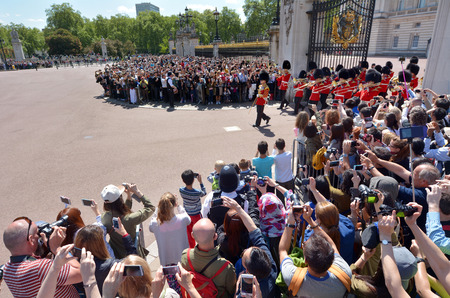 buckingham palace: LONDON - MAY 13 2015:Spactators view and photographing the Marching Band  during Changing the Guards ceremony at Buckingham Palace. Its one of most popular tourist attractions in London, UK
