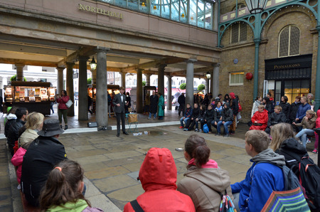 show garden: LONDON - MAY 15 2015:Spectators watching street show in Covent Garden in London, UK. Covent Garden is the only district in London to have a license for street performers and entertainers.