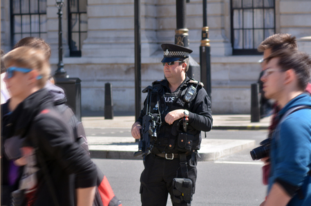 be alert: LONDON - MAY 12 2015:British counter terror police man on guard duty.Since Jan 2015 Police across Britain have been put on high alert and warned that they may be targeted in terror attacks