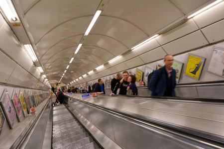 earls court: LONDON, UK - MAY 11 2015:Passengers on London Underground escalator. The first London Underground escalator was introduced at Earls Court in 1911.