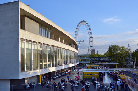 eye traveller: LONDON, UK - MAY 15 2015:Visitors outside the Royal Festival Hall in with London Eye in the background.Royal Festival Hall is a dance and talks venue within Southbank Centre in London. Editorial
