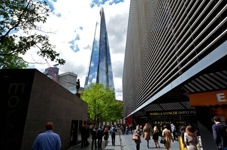 shard: LONDON, UK - MAY 13 2015:Pedestrians under The Shard skyscraper tower in London, UK.Standing 309.6 metres (1,016 ft) high,The Shard is currently the tallest building in the European Union.