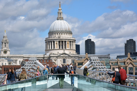 dominating: LONDON, UK - MAY 12 2015:St Pauls Cathedral as view from Millennium Bridge.The cathedral is one of the most famous and most recognisable sights of London, with its dome dominating the skyline for 300 years.