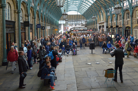 entertainers: LONDON - MAY 15 2015:Spectators watching street show in Covent Garden in London, UK. Covent Garden is the only district in London to have a license for street performers and entertainers.