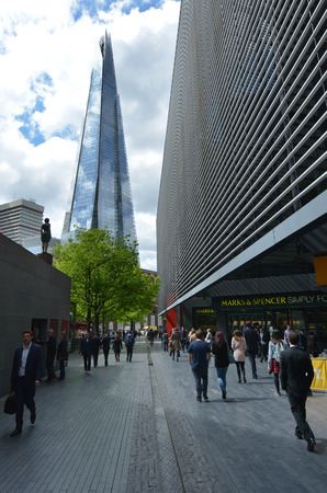 shard of glass: LONDON - MAY 13 2015:Pedestrians under The Shard skyscraper tower.The glass pyramidal tower has 72 floors with a viewing gallery and open-air observation deck at a height of 244.3 metres (802 ft). Editorial