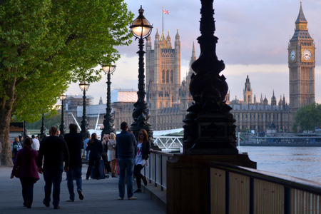 southbank: LONDON - MAY 15 2015:Visitors on Queens Southbank walk overlooking the Big Ben clock tower in of Westminster Palace.The tower is one of the most prominent symbols of the United Kingdom.