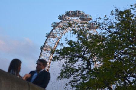romantic places: LONDON, UK - MAY 15 2015:Romantic couple under London Eye in London, UK.London Eye is on of the top 5 of most romantic places in London.