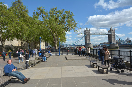 hamlets: LONDON, UK - MAY 12 2015:Visitors and The Tower Bridge spanning over River Thames as view from London borough of Tower Hamlets (north side) in London, UK.