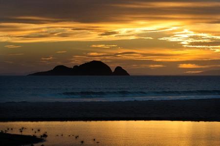 nz: Sunrise over Kiwi Island from Henderson bay  in Northland NZ.