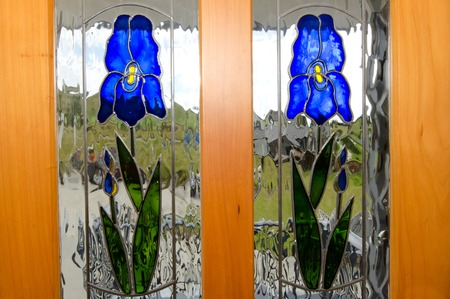 Two tained glass of purple Iris flowers on a window door. Stock Photo