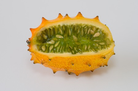 hedged: Kiwano or African horned melon sliced open over white background. Also known as hedged gourd, African Horned Cucumber, English tomato.