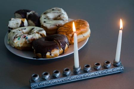 hanoukia: La premi�re bougie de Hanoukka avec chanukiah et la plaque avec des beignets. Banque d'images
