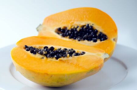 cutaneous: Papaya or Pawpaw fruit sliced in half isolated on a white background and white plate.