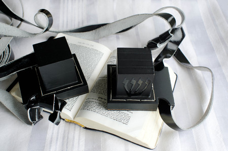 A set of tefillin includes the arm-tefillin (left) and the head-tefillin on a  praying book and Tallit. Stock Photo