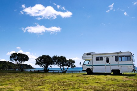 Camper van in a camp ground near the sea in a sunny summer day during travel vacation journey. Stock Photo