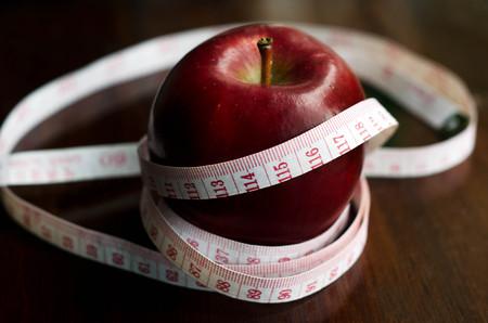 metro medir: Medición metros sobre una manzana dieta en la mesa de la cocina.