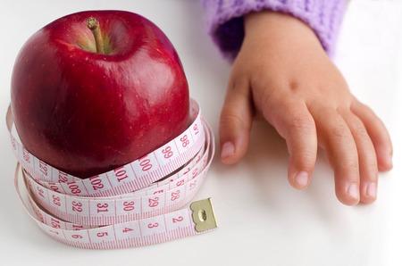 metro medir: Medición metros sobre una manzana dieta con la mano del niño. Foto de archivo