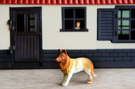 guard house: Concept photo: A toy guard dog guarding a house while a toy man watch out from his home window.